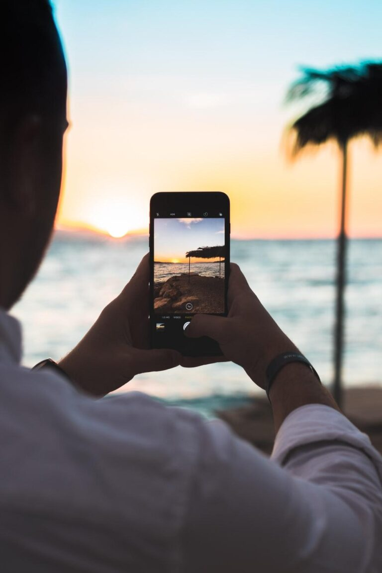 person taking photo of beach